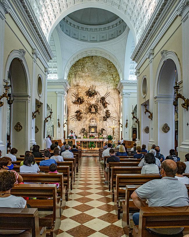 L'interno del santuario della madonna della corona durante una messa